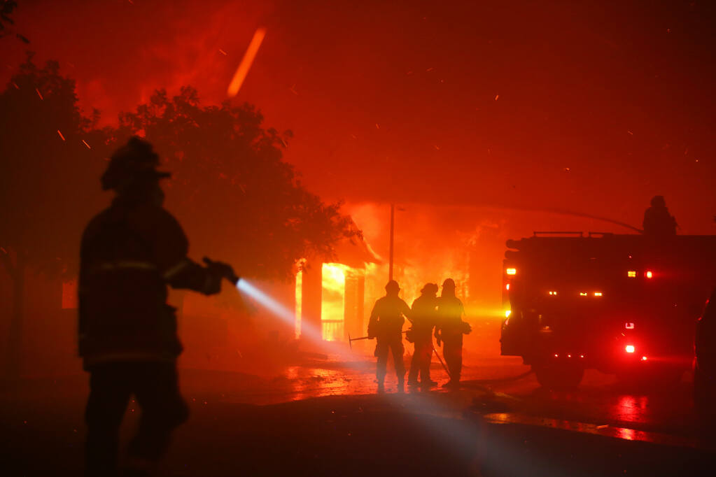 Firefighters work on slowing the spread of flames as the Shady fire takes out homes on Mountain Hawk Drive in Santa Rosa early Monday morning, September 28, 2020.  (Christopher Chung/ The Press Democrat)