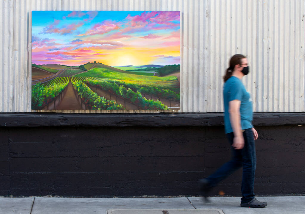 """A pedestrian walks past a mural by artist Audrey Maddigan-Martin, one of seven paintings from various artists that make up the new public art showcase: """"Greetings from The Barlow: A Postcard Tribute to Sonoma County,"""" at The Barlow in Sebastopol, California, on Wednesday, September 16, 2020. (Alvin A.H. Jornada / The Press Democrat)"""