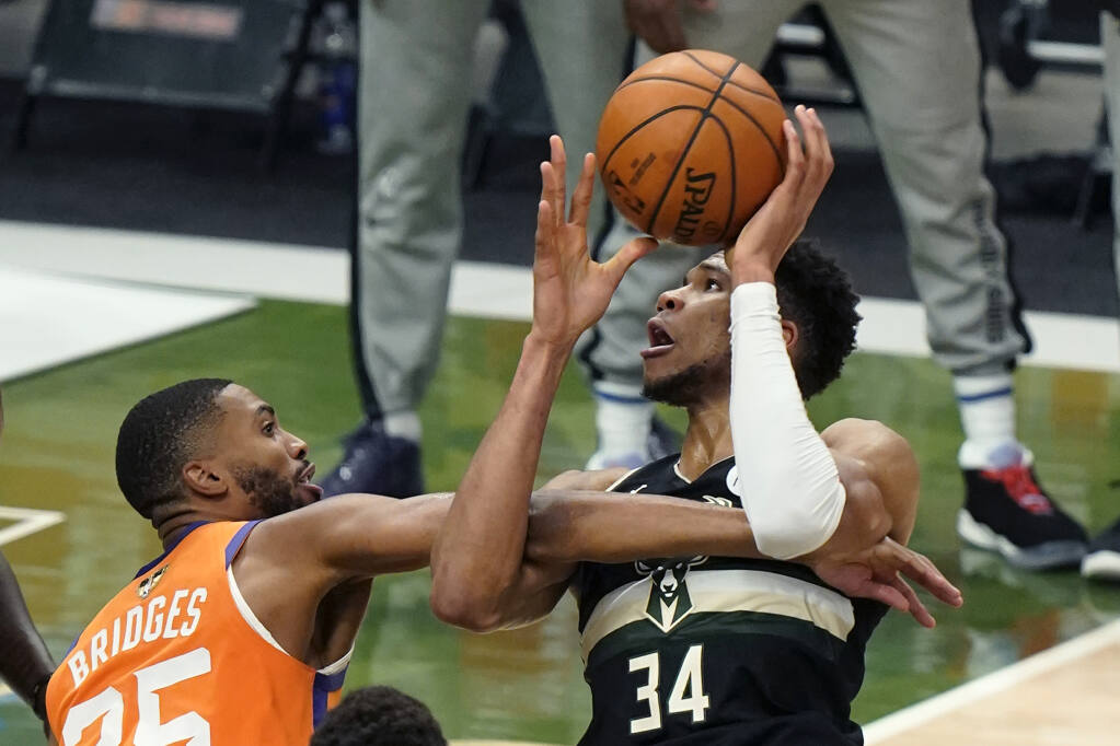 Milwaukee Bucks forward Giannis Antetokounmpo (34) battles under the basket against Phoenix Suns forward Mikal Bridges (25) during the first half of Game 6 of basketball's NBA Finals in Milwaukee, Tuesday, July 20, 2021. (AP Photo/Paul Sancya)