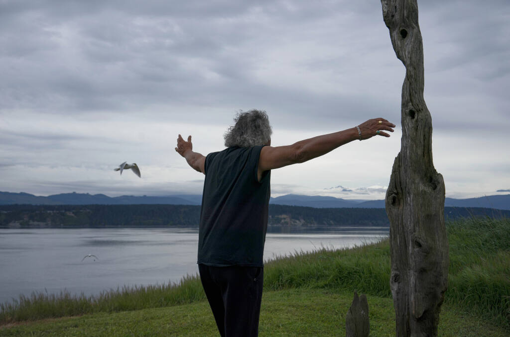 Marty Bluewater stretches his arms to hug a totem pole recently erected outside his home on Protection Island, about 2.5 miles from the coast of Cape George, Wash., April 28, 2021. Bluewater, 72, is the only person to have a lifetime tenancy on the roughly 370-acre, two-mile-long Protection Island, which was designated a National Wildlife Refuge in 1982. (Ruth Fremson/The New York Times)