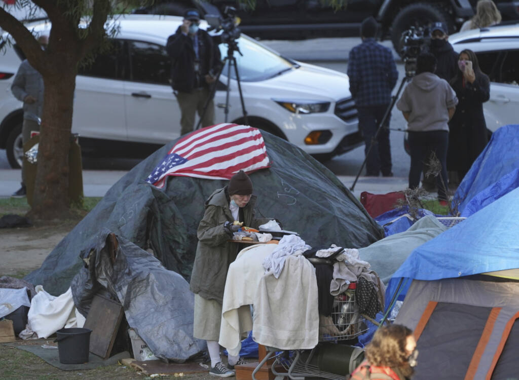 """FILE - In this March 24, 2021, file photo a woman eats at her tent at the Echo Park homeless encampment at Echo Park Lake in Los Angeles. A proposal by two Los Angeles city councilmen to set up temporary camps or """"tiny homes"""" for homeless people in beach parking lots is drawing opposition. The motion asks the city administrative officer to evaluate and identify funding for temporary sites for """"single-occupancy tiny homes or safe camping"""" at Will Rogers State Beach in Pacific Palisades, Dockweiler Beach in Playa del Rey and Fisherman's Village in Marina del Rey. (AP Photo/Damian Dovarganes, File)"""