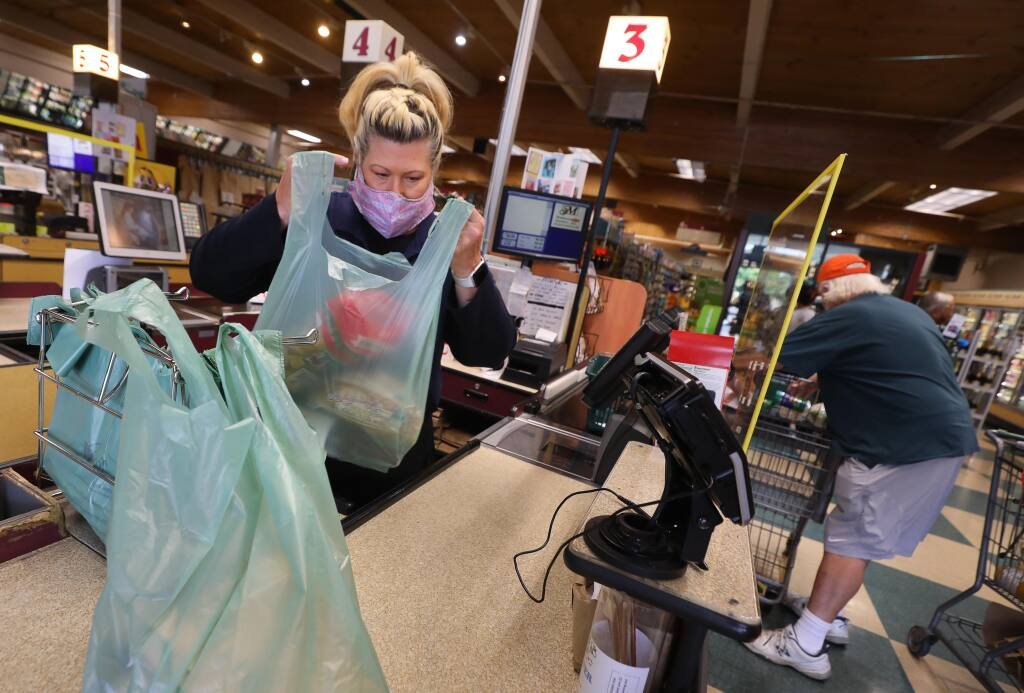 Cashier Michelle Paull bags a customer's purchases into plastic bags at Molsberry's Market in Santa Rosa on Thursday, July 16, 2020.  Grocery stores are beginning to allow the use reusable bags again, but customers are required to bag their own purchases, and refrain from placing personal bags onto high-touch surfaces such as checkout counters and conveyor belts.(Christopher Chung/ The Press Democrat)
