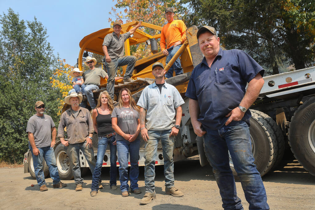 Jeff Parmeter, right, and members of the Parmeter Logging & Excavation crew, including Mike Burchfield, clockwise from bottom right, Heather Parmeter, Melinda Parmeter, Mike Parmeter, Ron Bei, William Harrison (holding his son William), Sean Nunez, and Charles Radtkey, along with many other Cazadero community members manned bulldozers and assisted to defend against the Walbridge fire. (Christopher Chung/ The Press Democrat)