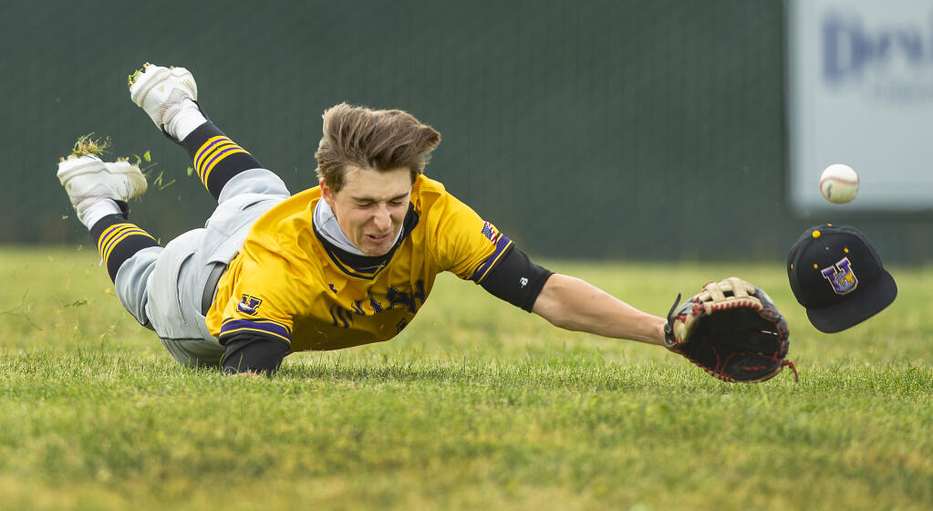Ukiah's Ethan Rinehart's hat flew off his head while diving for a pop-up to left field. Two runs scored as the ball went past Rinehart and Maria Carrillo went on to beat Ukiah, 7-1, on Friday, April 23, 2021. (Photo by John Burgess/The Press Democrat)