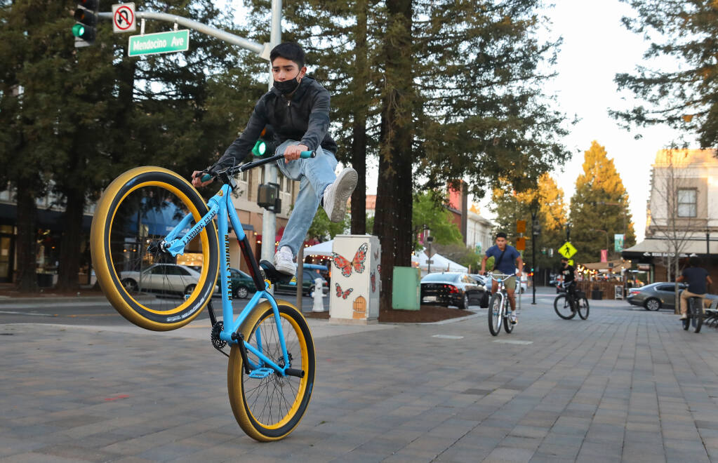 Alan Cortes and his friends perform tricks on their bikes while riding around Old Courthouse Square in Santa Rosa on Thursday, March 4, 2021.  (Christopher Chung / The Press Democrat)