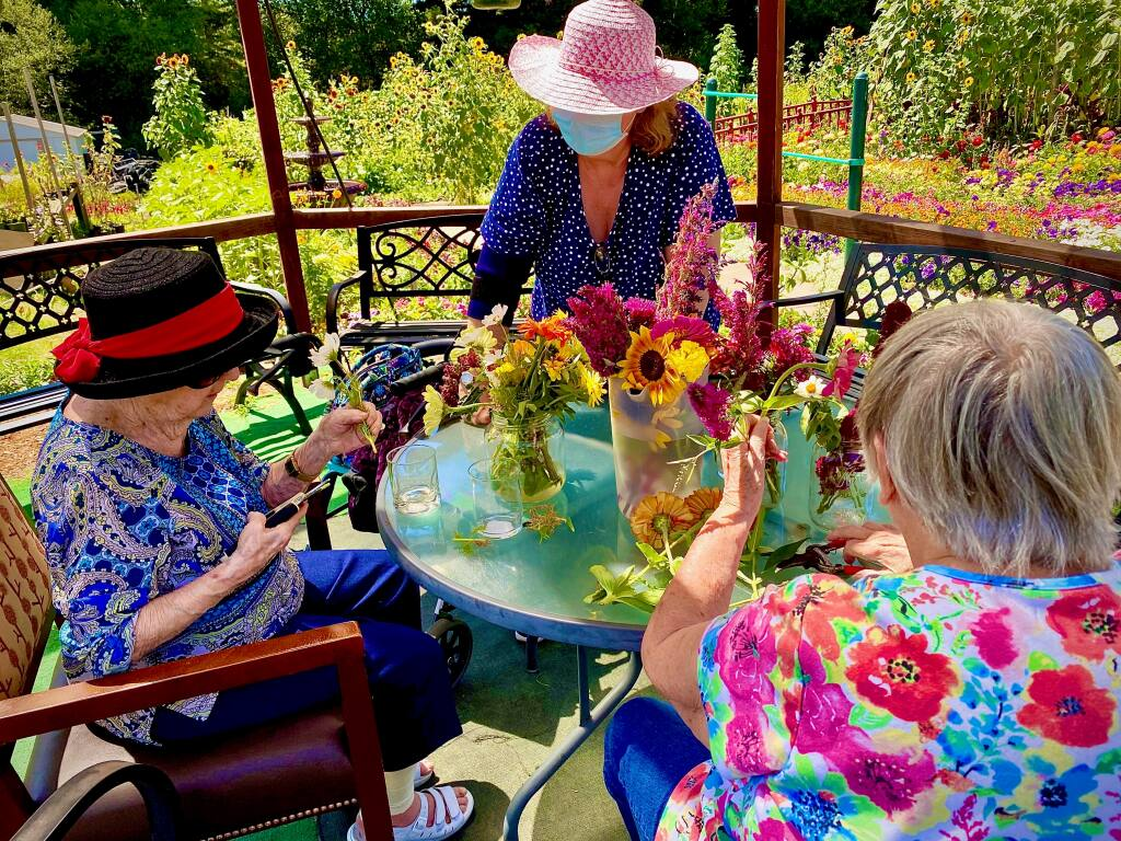 Residents of Healdsburg Senior Living gather on the patio for flower arranging. Some residential facilities for elders don't have outdoor space for residents weary of sheltering indoors. (Tony Fisher)