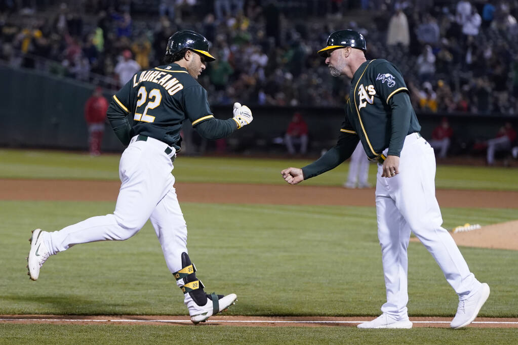 Oakland Athletics' Ramon Laureano, left, is congratulated by third base coach Mark Kotsay after hitting a three-run home run against the Los Angeles Angels during the seventh inning of a baseball game in Oakland, Calif., Monday, July 19, 2021. (AP Photo/Jeff Chiu)