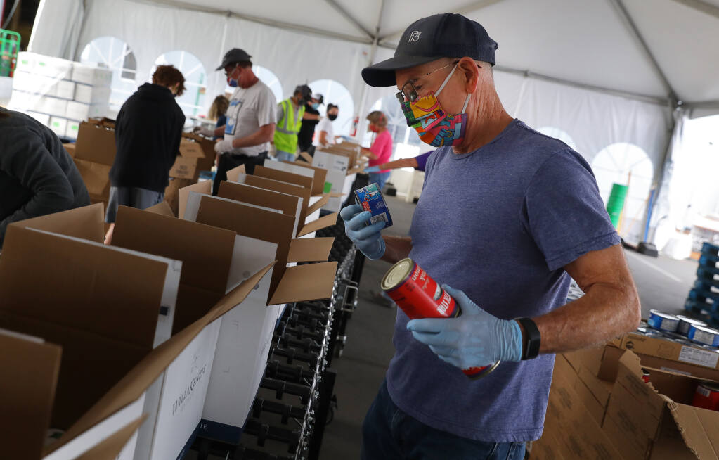 Volunteer Tom Chambers packs boxes of food at the Redwood Empire Food Bank in Santa Rosa on Friday, July 17, 2020.  (Christopher Chung/ The Press Democrat)
