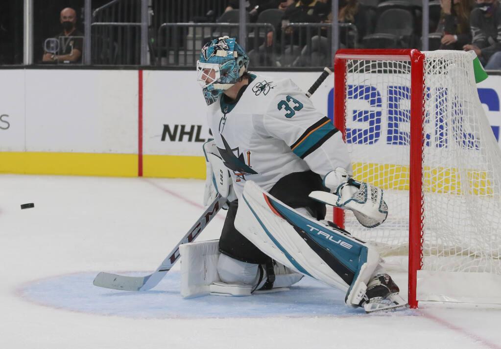 San Jose Sharks goaltender Adin Hill (33) deflects a shot in the second period of an NHL hockey preseason game Sunday, Sept. 26, 2021, in Las Vegas. The Sharks won 4-2. (AP Photo/Ronda Churchill)
