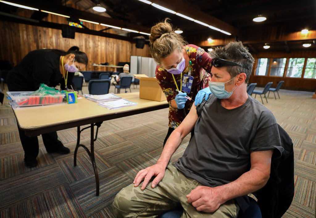 Santa Rosa Community Health registered nurse Natalie Hogan administers the Johnson & Johnson COVID-19 vaccine to Craig Petersen during a vaccine clinic for individuals in homeless shelters, at Alliance Redwoods near Occidental on Thursday, March 25, 2021.  (Christopher Chung / The Press Democrat)