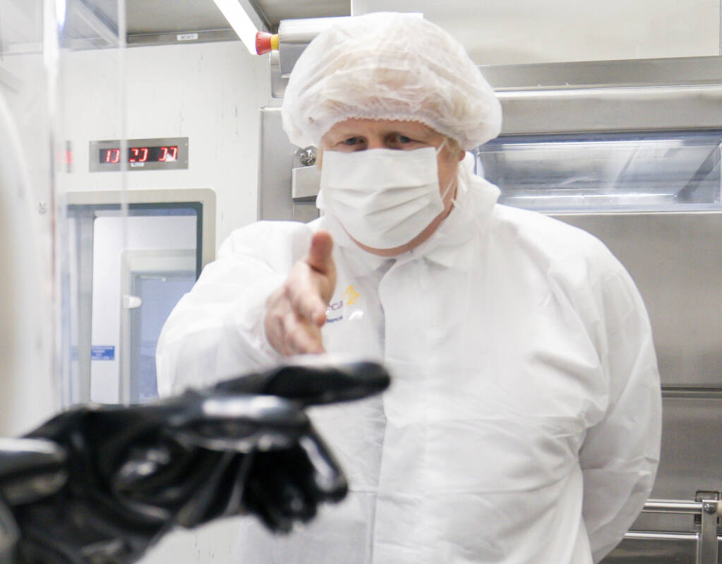 Britain's Prime Minister Boris Johnson visits AstraZeneca facility in Macclesfield, England, on Tuesday April 6, 2021, to learn more about their dollars 500 million investment into the site.  Johnson said Monday that Britain's vaccination program is going well and infections are falling, confirming that many shops and businesses will be allowed to reopen next week. (Dave Thompson/Pool via AP)
