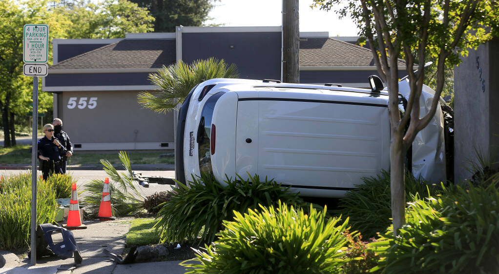 A driver was arrested Tuesday, May 4, 2021, after being pursued by Santa Rosa police after he ran a stop sign and ended up crashing into a business and running away on E Street in Santa Rosa.  (Kent Porter / The Press Democrat)