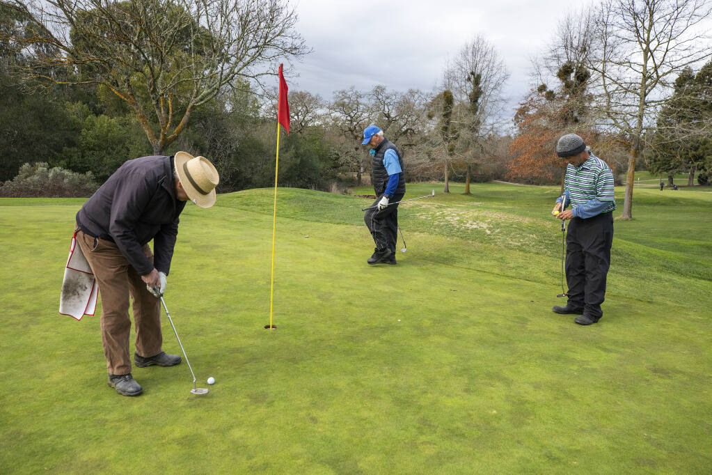 From left, golfing buddies Marvin Schouweiler, Fred Rose and Josh Hafner put out on the 6th green at the Bennett Valley Golf Course in Santa Rosa on Monday, February 1, 2021. The Santa Rosa City Council will study the golf course and it's potential future uses at the Tuesday meeting. (Photo by John Burgess/The Press Democrat)