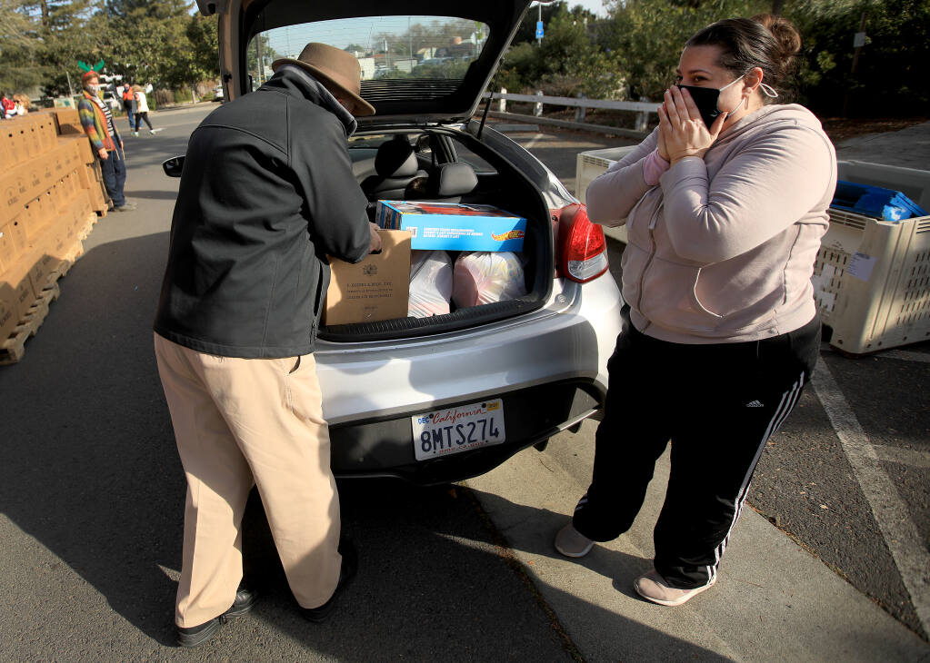 Sebastopol resident Elizabeth Fugere is overcome with emotion as Tim Passage of the Rotary Club of Sebastopol loads her car with groceries, Thursday, Dec. 24, 2020 in the parking lot of the Sebastopol Center for the Arts. (Kent Porter / The Press Democrat) 2020