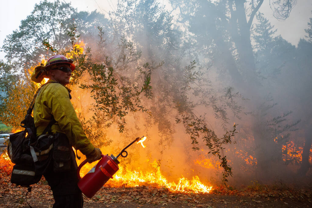 City of Corona fire captain Roger Williams keeps an eye on conditions during a defensive firing operation around homes on Spring Mountain Road near St. Helena, California, on Thursday, Oct. 1, 2020. (Alvin A.H. Jornada / The Press Democrat)