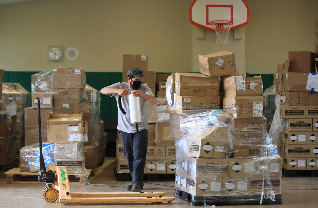 Sonoma County Office of Education employee Jorge Torres wraps Personal Protection Equipment to be readied for shipment to Sonoma County Schools, Wednesday, July  29, 2020.  The shipment, received from the state, will outfit district schools for about two months.  (Kent Porter / The Press Democrat) 2020