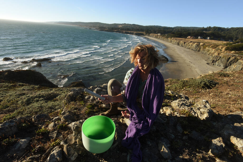 Margaret Lindgren, founder Unbeaten Path Tours using one of her crystal sound bowl at Black Point Beach in Annapolis, Calif. on Thursday, Aug. 20, 2020. (Erik Castro/For The Press Democrat)