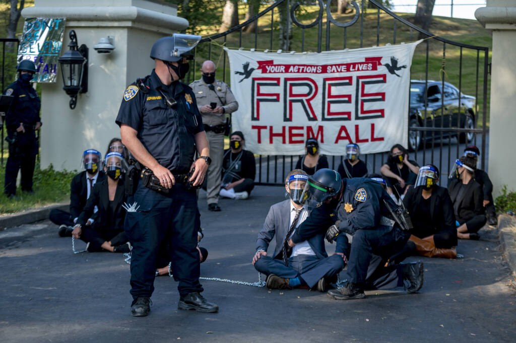 A California Highway Patrol officer inspects a chained protester outside of California Gov. Gavin Newsom's mansion in Fair Oaks, Calif., on Monday, July 27, 2020. Demonstrators chained themselves to a fence outside the governor's home, calling for mass inmate releases and an end to immigration transfers because of the coronavirus pandemic, as deaths mounted at a San Francisco Bay Area prison. (Daniel Kim/The Sacramento Bee via AP)