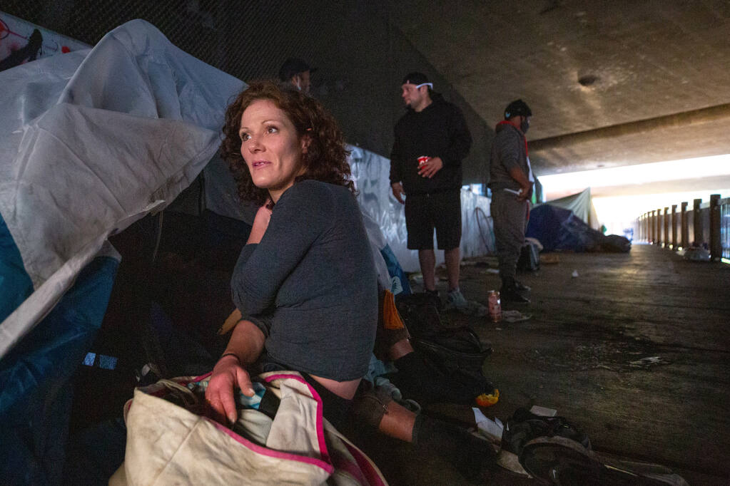 Jennifer McDonough, who has been homeless off and on for the past nine years, sits at her tent on Prince Memorial Greenway beneath Highway 101 in Santa Rosa on Tuesday, Dec. 8, 2020. (Alvin A.H. Jornada / The Press Democrat)