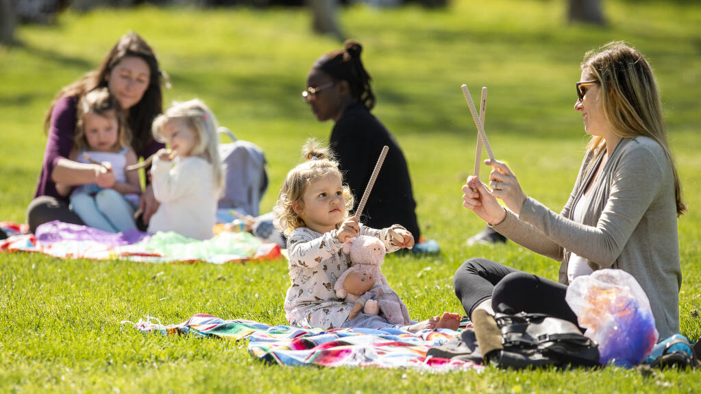 From left, mom Felice plays with twin daughter Sarah and Analise Toth, 2 1/2, along with Nonny Ndawo, while Liv, 2, shows her mom, Madison Hollander, how to make music with sticks during the Music Together music and movement outdoor class at the Healdsburg Community Center on Thursday, April 1, 2021. (John Burgess / The Press Democrat)