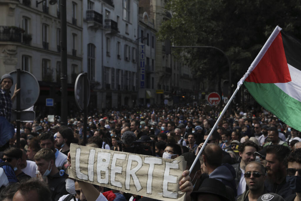 Protestors hold up a banner which reads 'freedom' in French during a demonstration in Paris, France, Saturday, July 31, 2021. Demonstrators gathered in several cities in France on Saturday to protest against the COVID-19 pass, which grants vaccinated individuals greater ease of access to venues. (AP Photo/Adrienne Surprenant)