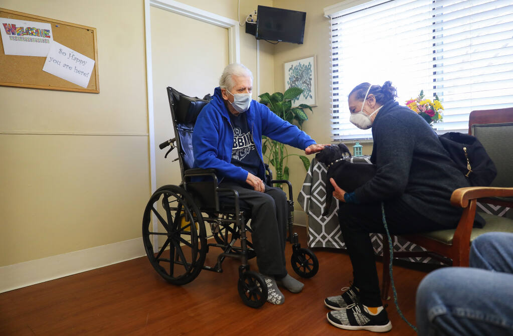 Tommy Phillips, left, pets Thunderbolt during a visit by his sister, Patty Feerick, at the Windsor Care Center of Petaluma on Friday, March 19, 2021.  The care facility set up a special visitation room for its care residents. (Christopher Chung/ The Press Democrat)