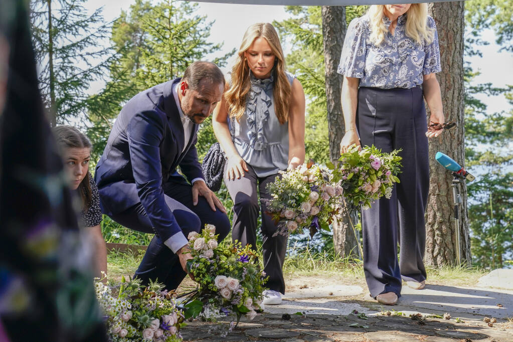 Crown Prince Hakon and Princess Ingrid Alexandra, with Crown Princess Mette-Marit obscured right, lay flowers at the July 22 memorial during the memorial service on Utoya. Commemorations to mark 10-years since Norway's worst ever peacetime slaughter when right wing extremist Anders Breivik set off a bomb in the capital, Oslo, killing eight people, before heading to tiny Utoya island where he stalked and shot dead 69 mostly teen members of the Labor Party's youth wing. (Torstein Boe / NTB via AP)
