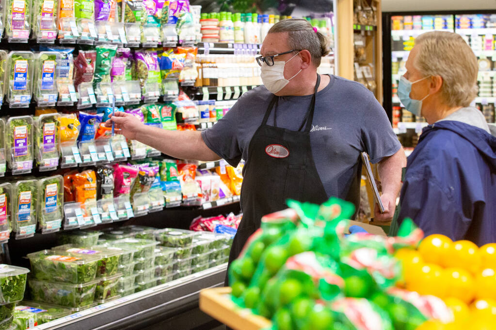 Produce department manager Rocket Burton, left, talks with clerk Douglas Kearns in front of the display of packaged greens at Oliver's Market in Windsor, California, on Tuesday, Jan. 12, 2021. (Alvin A.H. Jornada / The Press Democrat)