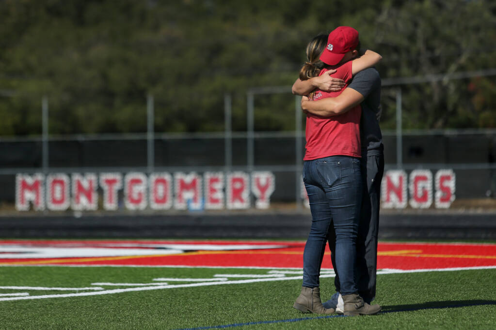 Montgomery High track and field head coach Melody Karpinski hugs former student-athlete Worthy Gutierrez who stopped by Wednesday to check in on the team after their coach Bryan Bradley, 43, died Tuesday. Photo taken at Montgomery High School in Santa Rosa, Calif., on Wednesday, August 25, 2021.(Beth Schlanker/The Press Democrat)