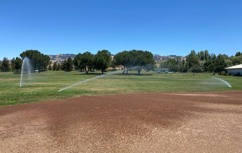 Sprinklers blast water onto the grass at Prince Park in east Petaluma shortly after noon on Tuesday, June 15, 2021. Residents questioned the city's irrigation timing, which contradicted guidance city officials put out to stem impacts from the ongoing drought. (EMILY CHARRIER/ARGUS-COURIER STAFF)