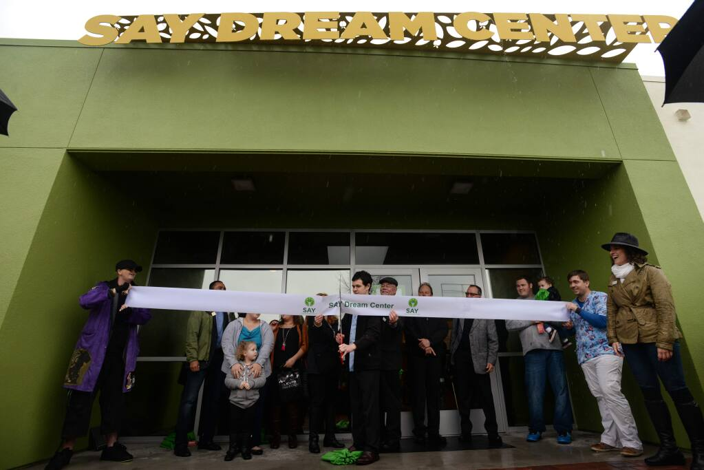 Cameron Vadnais, a formerly homeless youth, cuts the ribbon to open Social Advocate's for Youth's Dream Center in 2016. (ERIK CASTRO / For The Press Democrat)