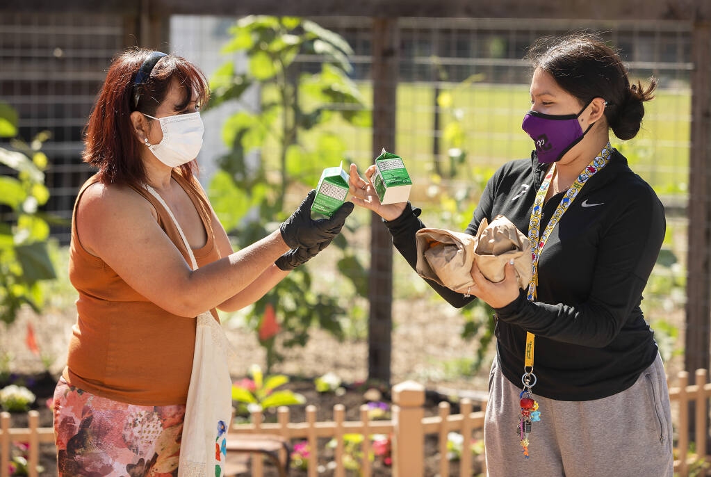Elizabeth Tlatilpa, left, helps Alexandra Herrera find an extra finger to hold two free lunches for her children at the Bayer Farm in Santa Rosa on Wednesday, June 9, 2021. The Redwood Empire Food Bank offers free, healthy meals to children and teens across Sonoma County from June 7th through August 6th across Sonoma County.  (Photo by John Burgess/The Press Democrat)