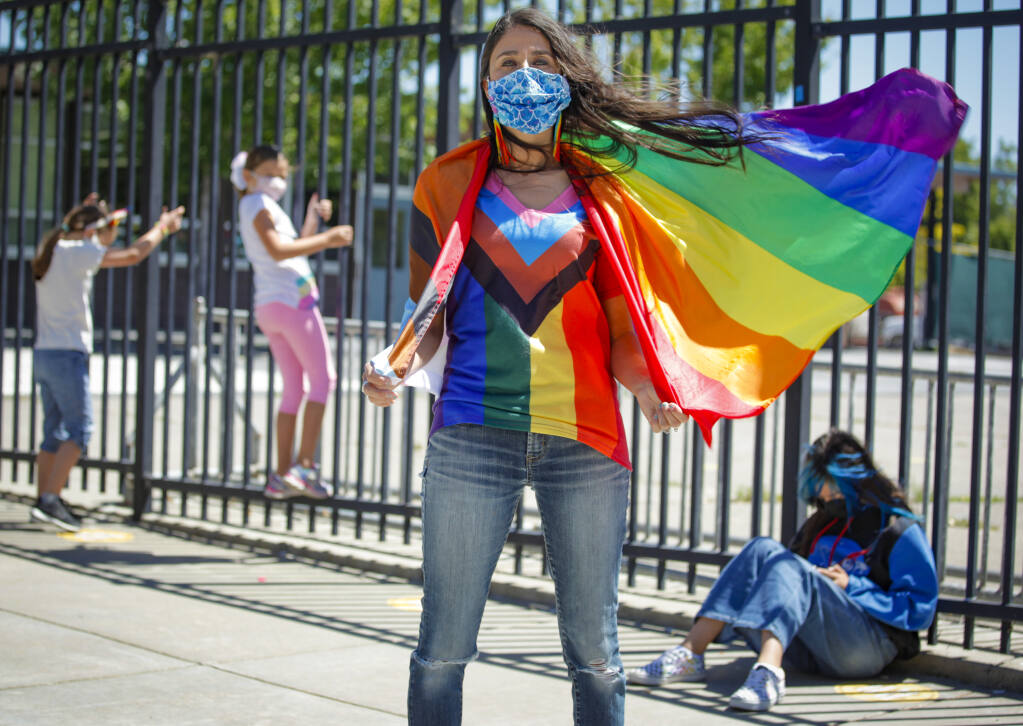 Renee Ho, founder of Amor Para Todos (Love for All), a grassroots nonprofit based in Petaluma whos mission is to support and ensure the safety of LGBTQIA+ students holds a Pride flag raised on an Old Adobe Union School District school campus for Pride month. Behind her are members of the APT student club of Loma Vista Immersion Academy. _ Monday, June 07, 2021, Petaluma, CA, USA._(CRISSY PASCUAL/ARGUS-COURIER STAFF)