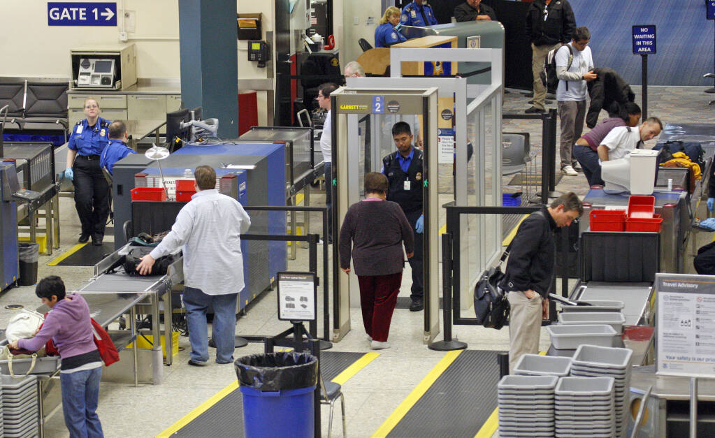 FILE - This Jan. 5, 2010 file photo shows air travelers and their carry-on luggage being screened by Transportation Security Administration employees before boarding aircraft at Oakland International Airport in Oakland, Calif. (AP Photo/Ben Margot, File)