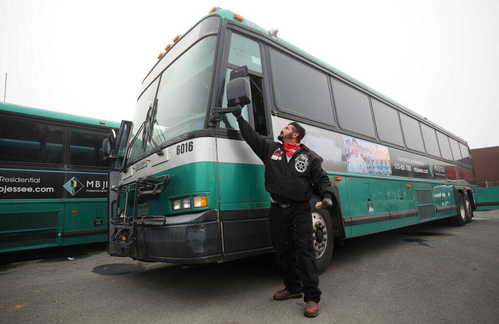 Robert Conklin wipes off a side mirror of one of the three buses being driven across the country by local Teamsters in Santa Rosa on Thursday, Sept. 17, 2020. The three buses and an ambulance are being delivered to Haiti through Those Angels, Inc. (Christopher Chung / The Press Democrat)