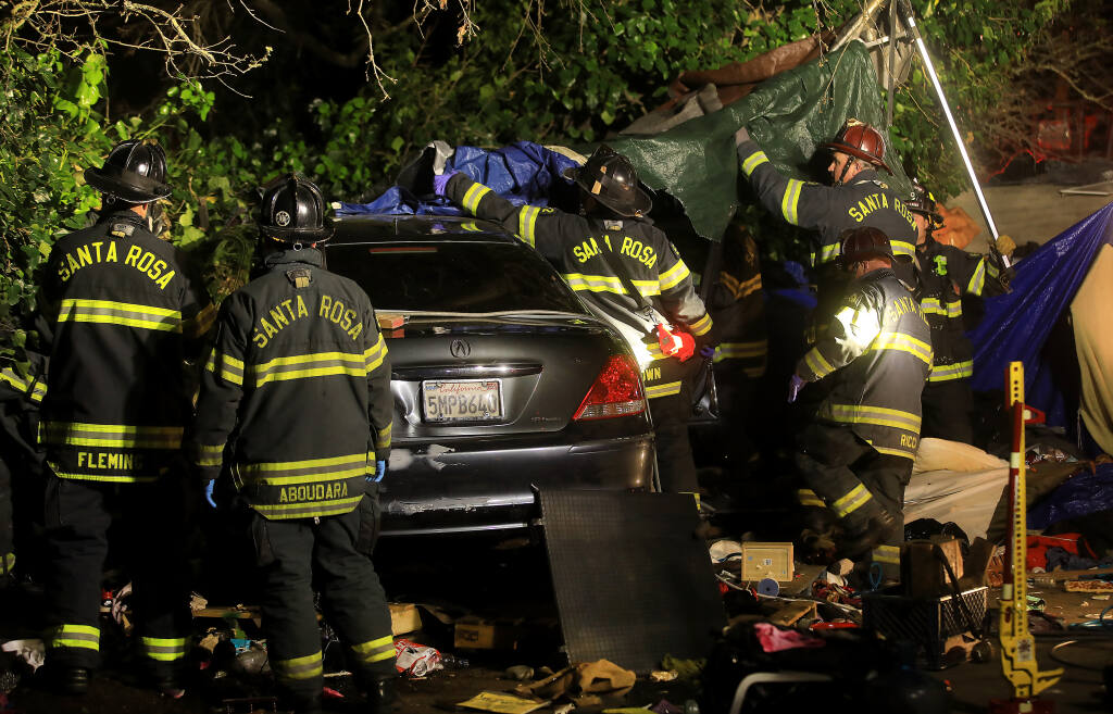 Santa Rosa firefighters clear the area around a car that plowed in to a homeless encampment in order to free a woman pinned underneath the vehicle on Roberts Avenue in Santa Rosa, Tuesday, March 23, 2021. (Kent Porter / The Press Democrat)