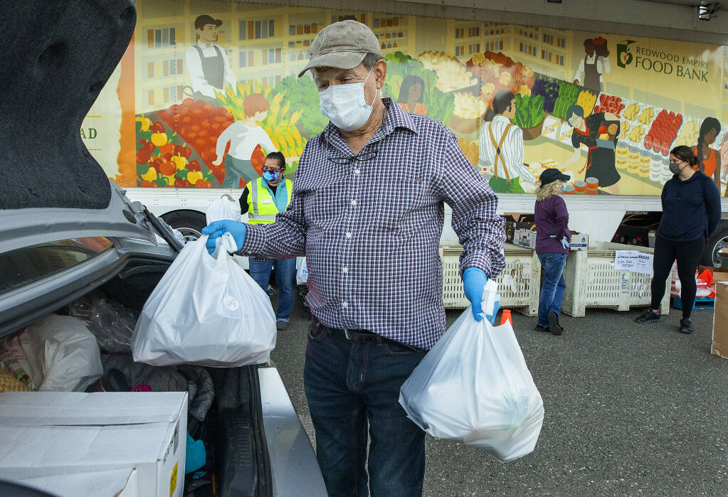 Zeke Guzman, President of Latinos Unidos del Condado de Sonoma, loads bags of food for people in needs while volunteering at the Redwood Empire Food Bank distribution on Wednesday evening, January 20, 2021.  (Photo by John Burgess/The Press Democrat)