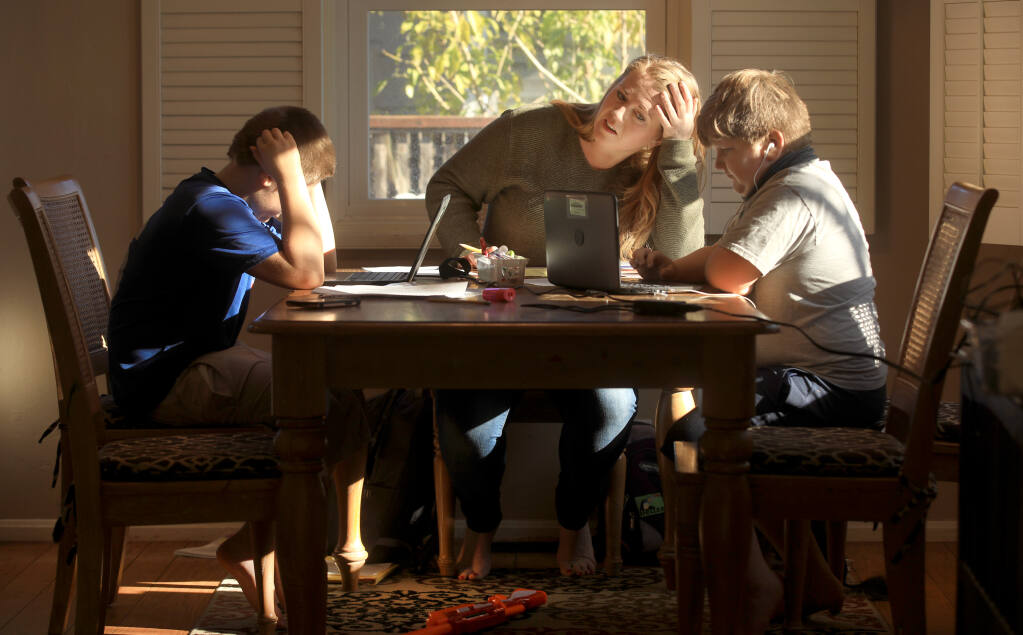 Tracy Kline pulls double schoolwork duty with her two sons, Cooper Baron, left, 9, and Parker Baron, right, just before starting a work conference call for herself, Friday, Feb. 5, 2021 at their home in Santa Rosa. (Kent Porter / The Press Democrat) 2021