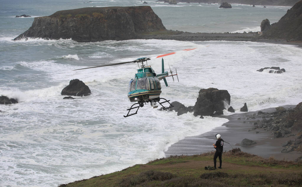 Henry 1, the Sonoma County Sheriff's helicopter team, Monday, Jan. 4, 2021, was called in to help search for two missing children that were swept away in the surf at Blind Beach, right, that also killed their father Sunday afternoon.  Goat Rock is in the background. (Kent Porter / The Press Democrat) 2021