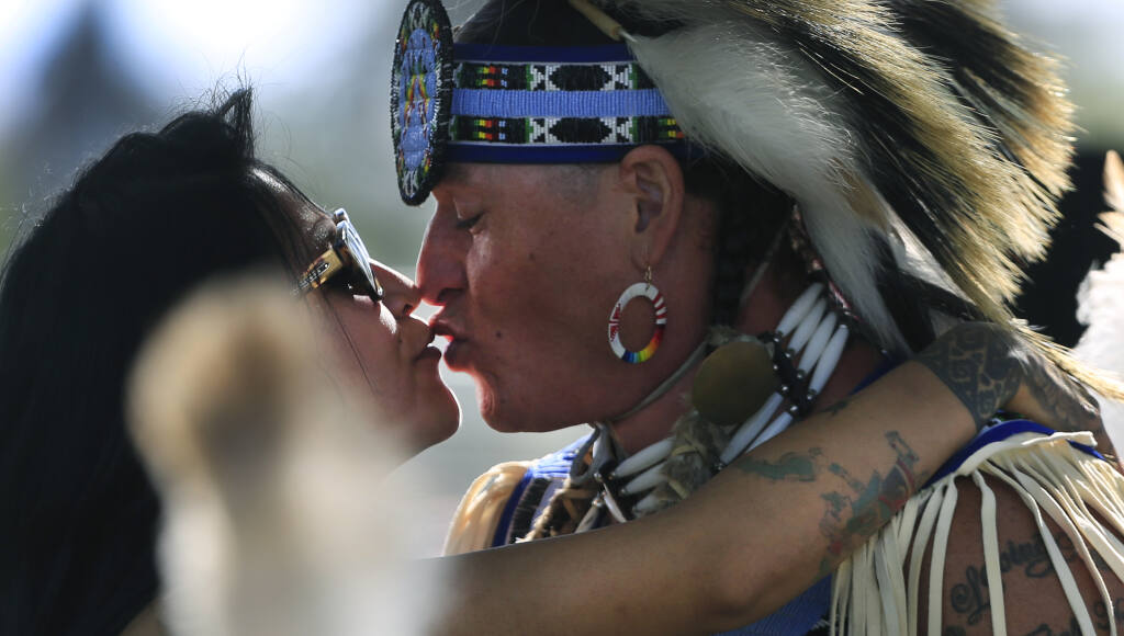 Lucero Vargas and Reuben Crowfeather of Santa Rosa, share a quiet moment during an Indigenous Peoples Gathering at the Sonoma County Fairgrounds in Santa Rosa, Saturday, May 1, 2021. Crowfeather, a Lakota Native American, recently moved to Sonoma County from Standing Rock, South Dakota. (Kent Porter / The Press Democrat) 2021