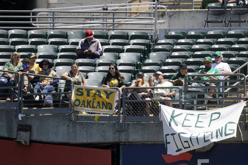 Fans sit behind a sign that reads Stay in Oakland during the first inning of a baseball game between the Oakland Athletics and the Los Angeles Angels in Oakland, Calif., Tuesday, July 20, 2021. (AP Photo/Jeff Chiu)