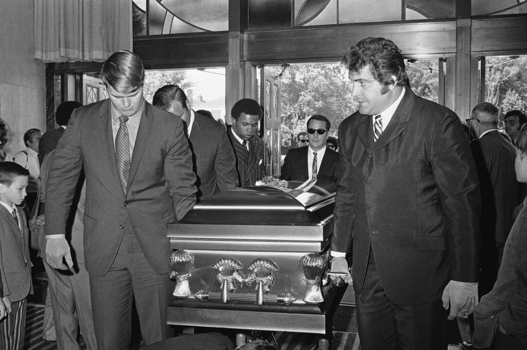 FILE  - In this June 19, 1970, file photo. Chicago Bears teammates of Brian Piccolo carry his coffin into Christ the King Church for funeral services in Chicago. From left, front to back, are Randy Jackson, Dick Butkus and Gale Sayers. Ed O'Bradovich is at right. Hall of Famer Gale Sayers, who made his mark as one of the NFL's best all-purpose running backs and was later celebrated for his enduring friendship with a Chicago Bears teammate with cancer, has died. He was 77. Nicknamed 'The Kansas Comet' and considered among the best open-field runners the game has ever seen, Sayers died Wednesday, Sept. 23, 2020, according to the Pro Football Hall of Fame. (AP Photo/File)