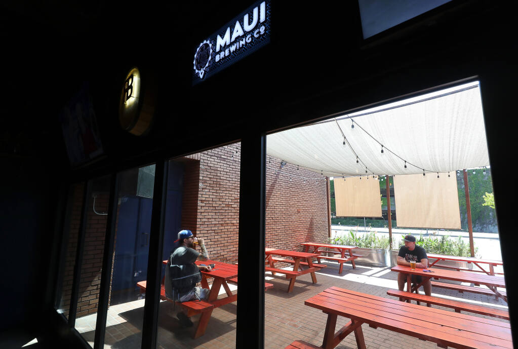 David Finkelstein, left, and Brooks Emerson drink beer in the outdoor patio of Flagship Taproom in Santa Rosa on Monday, July 13, 2020.  The taproom closed its indoor seating area Monday due to reinstated coronavirus restrictions.  (Christopher Chung/ The Press Democrat)