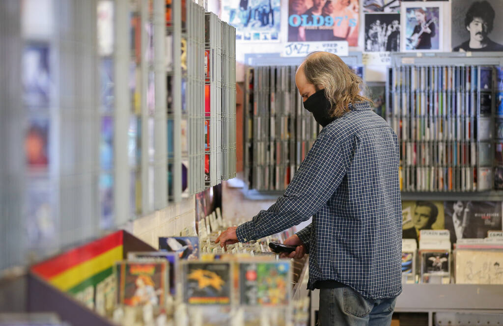 "Michael ""Hoyt"" Wilhelm looks for a compact disc for a person on the phone at The Last Record Store in Santa Rosa on Tuesday, March 23, 2021. (Christopher Chung / The Press Democrat)"