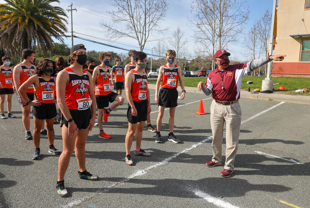 Piner cross-country coach Luis Rosales, right, tells Santa Rosa junior varsity runners that they can lower their masks if they feel comfortable after the first 100 meters of the race in Santa Rosa on Wednesday, March 3, 2021. (Christopher Chung / The Press Democrat)