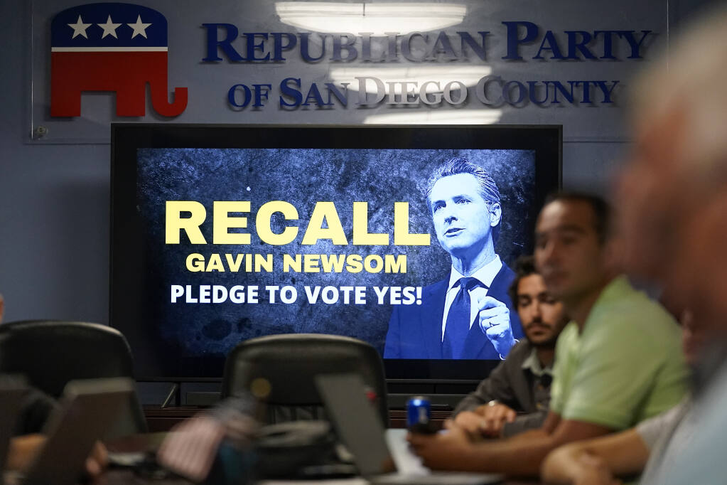 People listen during a meeting of volunteers to get out the vote by supporters of the effort to recall California Gov. Gavin Newsom at the San Diego Republican Party Headquarters, Monday, Sept. 13, 2021, in San Diego. Republicans led by former President Donald Trump are already claiming California's gubernatorial recall election is rigged. That messaging poses a problem for Republican Party officials, who are encouraging everyone to vote while maintaining concerns about the state's election security. (AP Photo/Gregory Bull)