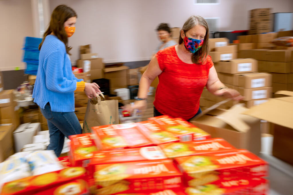Lynne Gordon Moquete, executive director of Una Vida, and a corps of volunteers pack bags of food that are being given away to the local community, at Hillside Church in Petaluma, California, on Tuesday, Oct. 6, 2020. (Alvin A.H. Jornada / The Press Democrat)