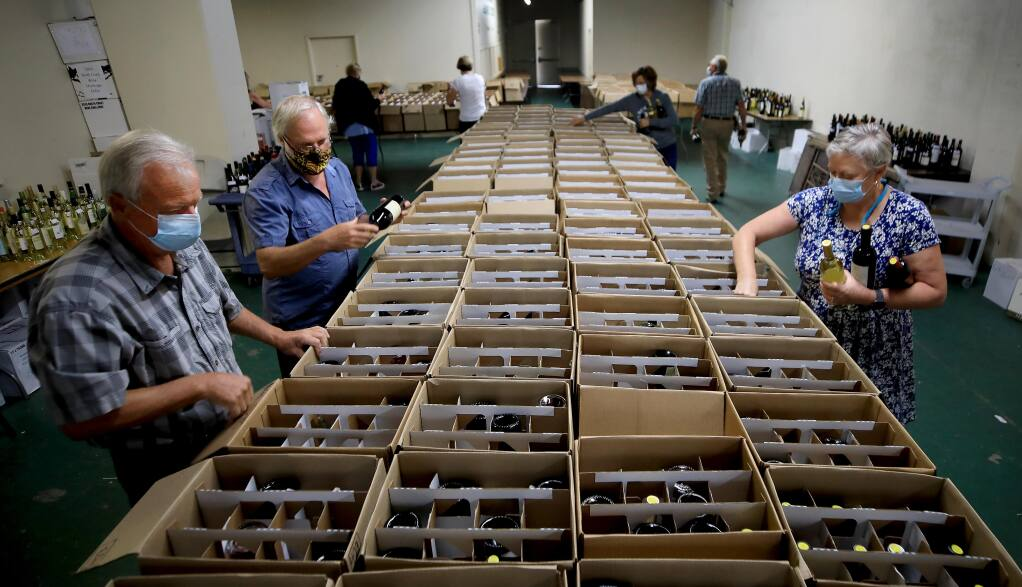 Volunteers for the North Coast Wine Challenge sort wines to be judged, Wednesday, July 15, 2020 at the Sonoma County Fairgrounds in Santa Rosa. (Kent Porter / The Press Democrat) 2020