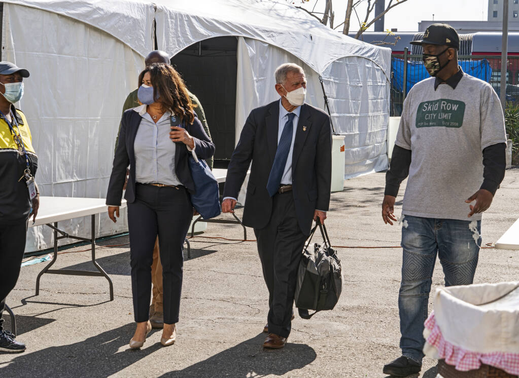 FILE - In this Feb. 4, 2021, file photo, Jeff Page, right, also known as General Jeff, a homelessness activist and leader in the Downtown Los Angeles Skid Row Neighborhood Council, walks with U.S. District Court Judge David O. Carter, middle, and Michele Martinez, special master on the issues of homelessness, after a court hearing at Downtown Women's Center in Los Angeles. Carter, a federal judge overseeing a sweeping lawsuit about the homelessness crisis in Los Angeles on Wednesday, May 26, chided the city and county of LA for their slow progress in providing shelter for thousands of unhoused residents who live near freeways. (AP Photo/Damian Dovarganes, File)