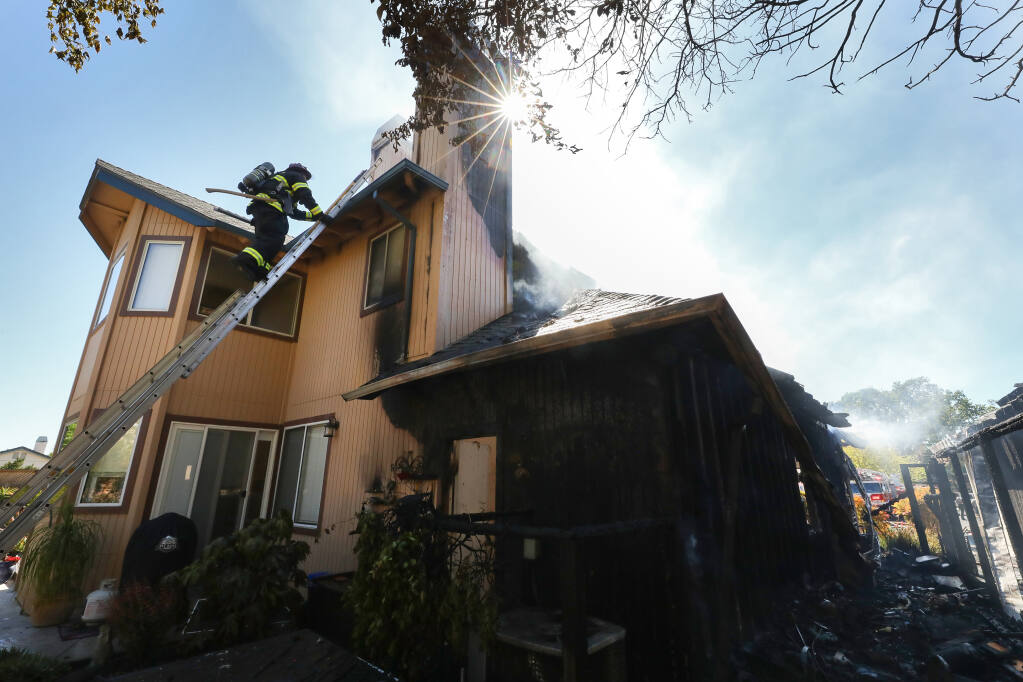 Sonoma County Fire District Capt. Fred Leuenberger climbs a ladder onto the roof of a house to vent a chimney on Pistachio Place in Windsor on Tuesday, April 27, 2021. (Christopher Chung / The Press Democrat)